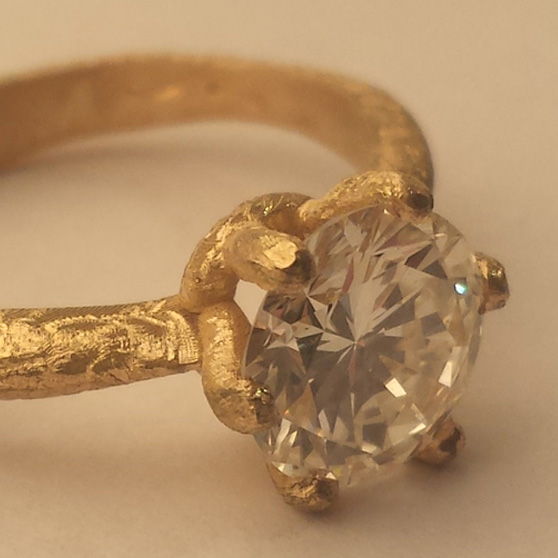Anello in oro grezzo con diamante fotografato di tre quarti