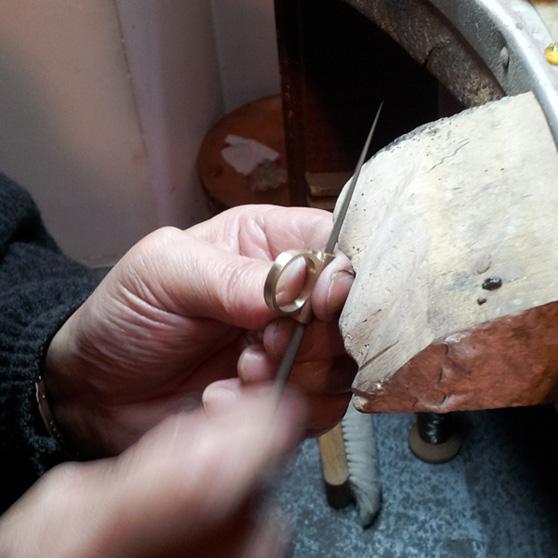 Un artigiano orafo rifinisce un anello