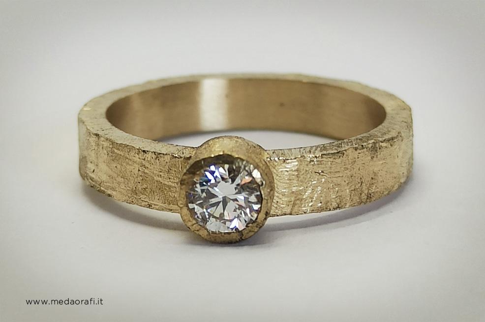 Anello di fidanzamento in oro giallo e diamante solitario realizzato con fascia a bordi squadrati e trattanento della superficie a grezzo