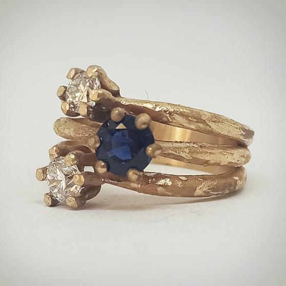 Anello di fidanzamento modello Materia in oro rosa trattato a grezzo versione trilogy con 2 diamanti e zaffiro fissati su tre differenti anelli uniti alla base