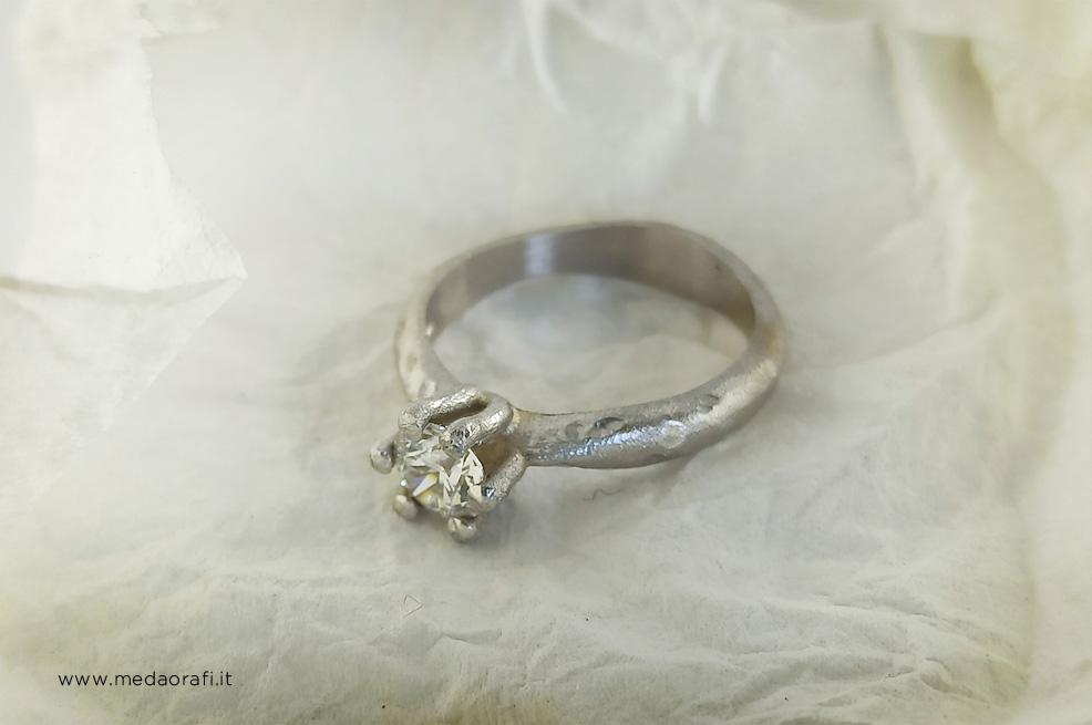 Anello di fidanzamento in oro bianco 18 kt e diamante in un cartina spiegazzata