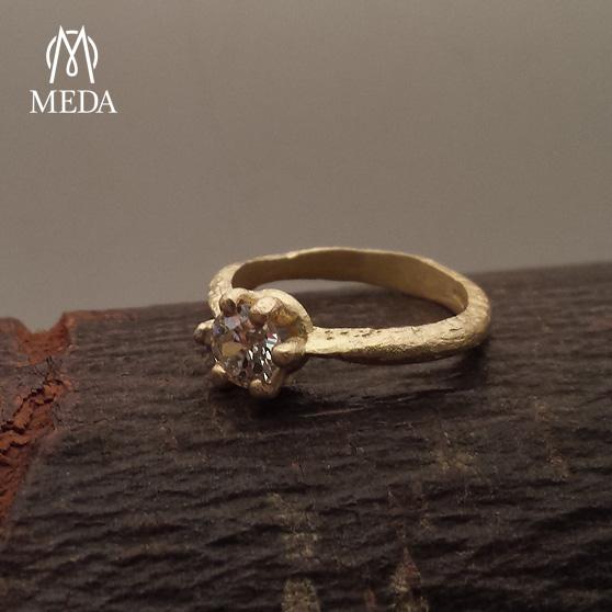 Anello solitario in oro grezzo e diamante su un ciocco di legno