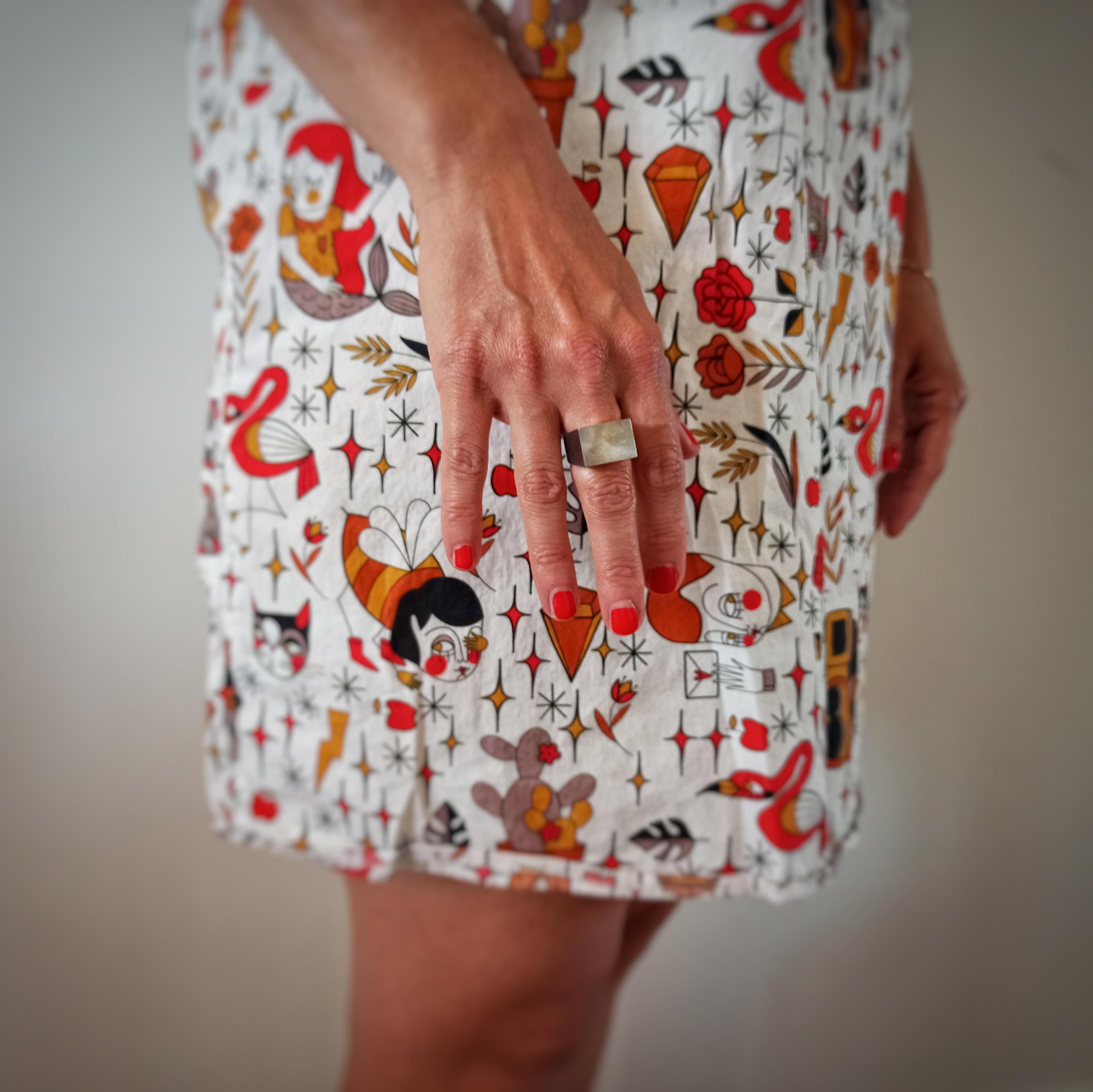 Mano di donna con anelli in acciaio e vestito fantasia