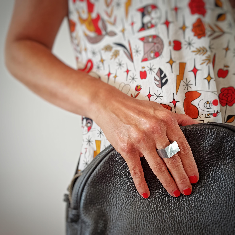 Mano di donna che indossa anello di desgin in acciaio e una borsa in pelle