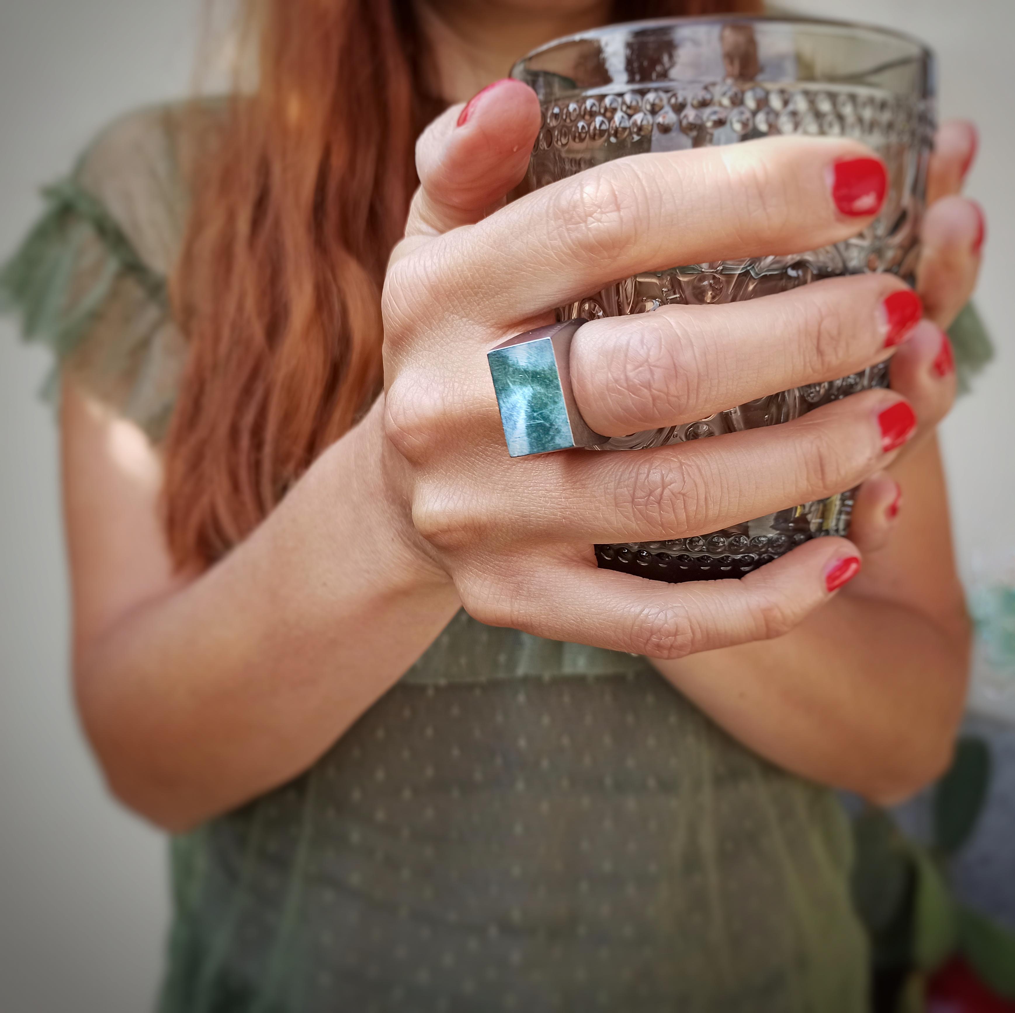 Una donna afferra un bicchiere di cristallo con un anello Bullone in acciaio