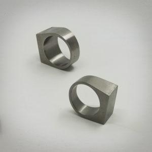 Due anelli in acciaio appoggiati in piedi per mostrare l'interno