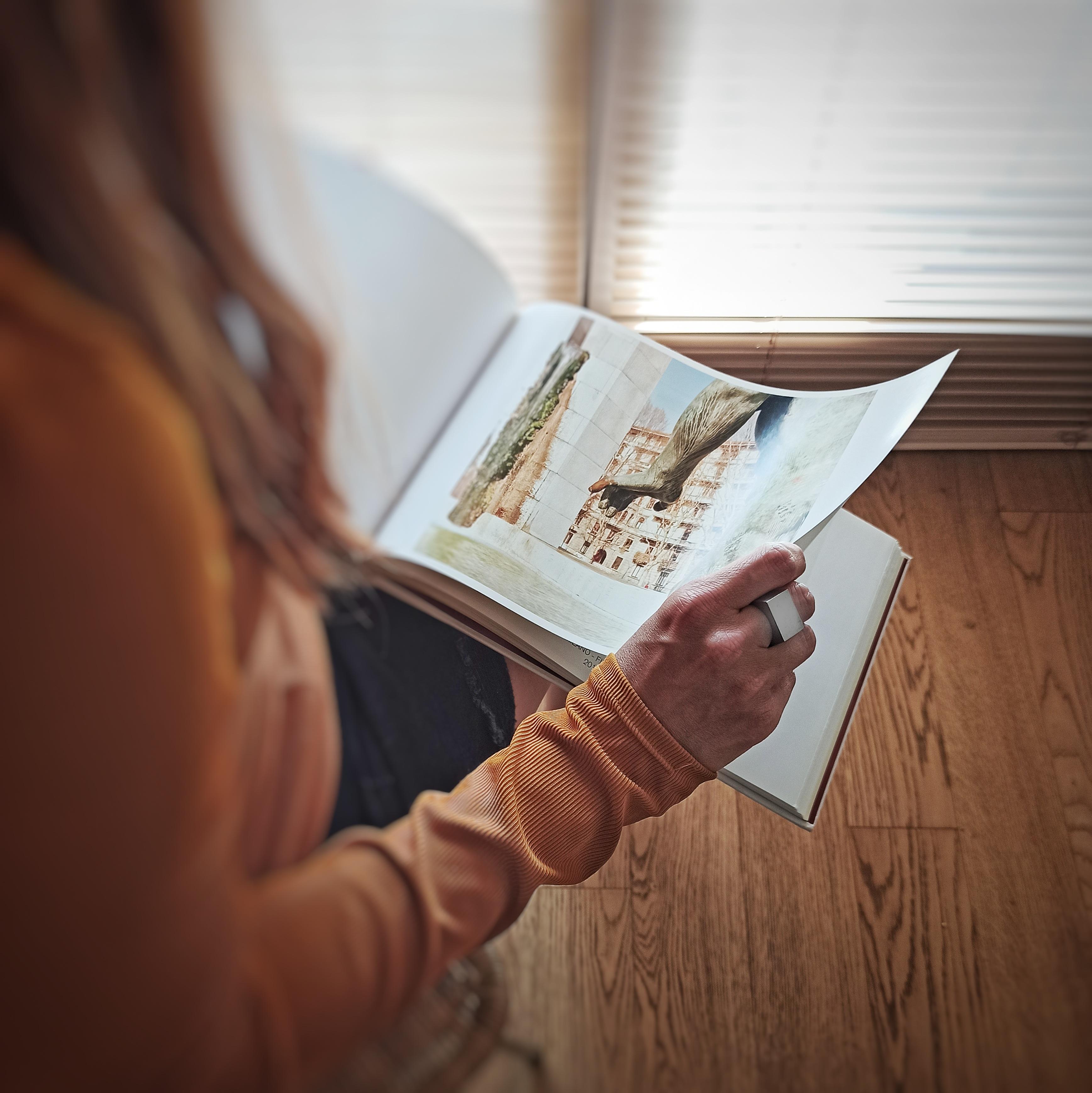 Una donna sfolia un libro di fotografia con un anello Bullone in acciaio