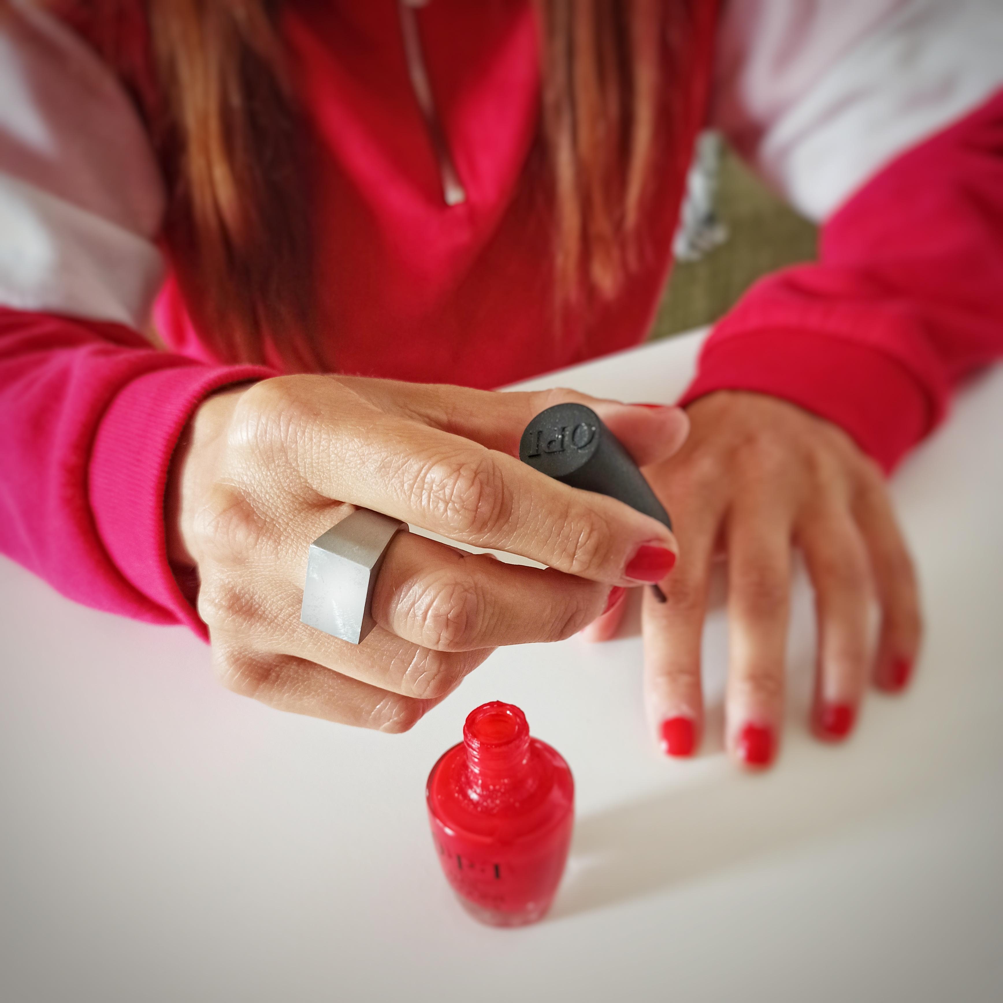 Mani di donna con anello in aciaio mentre applicano lo smalto per unghie