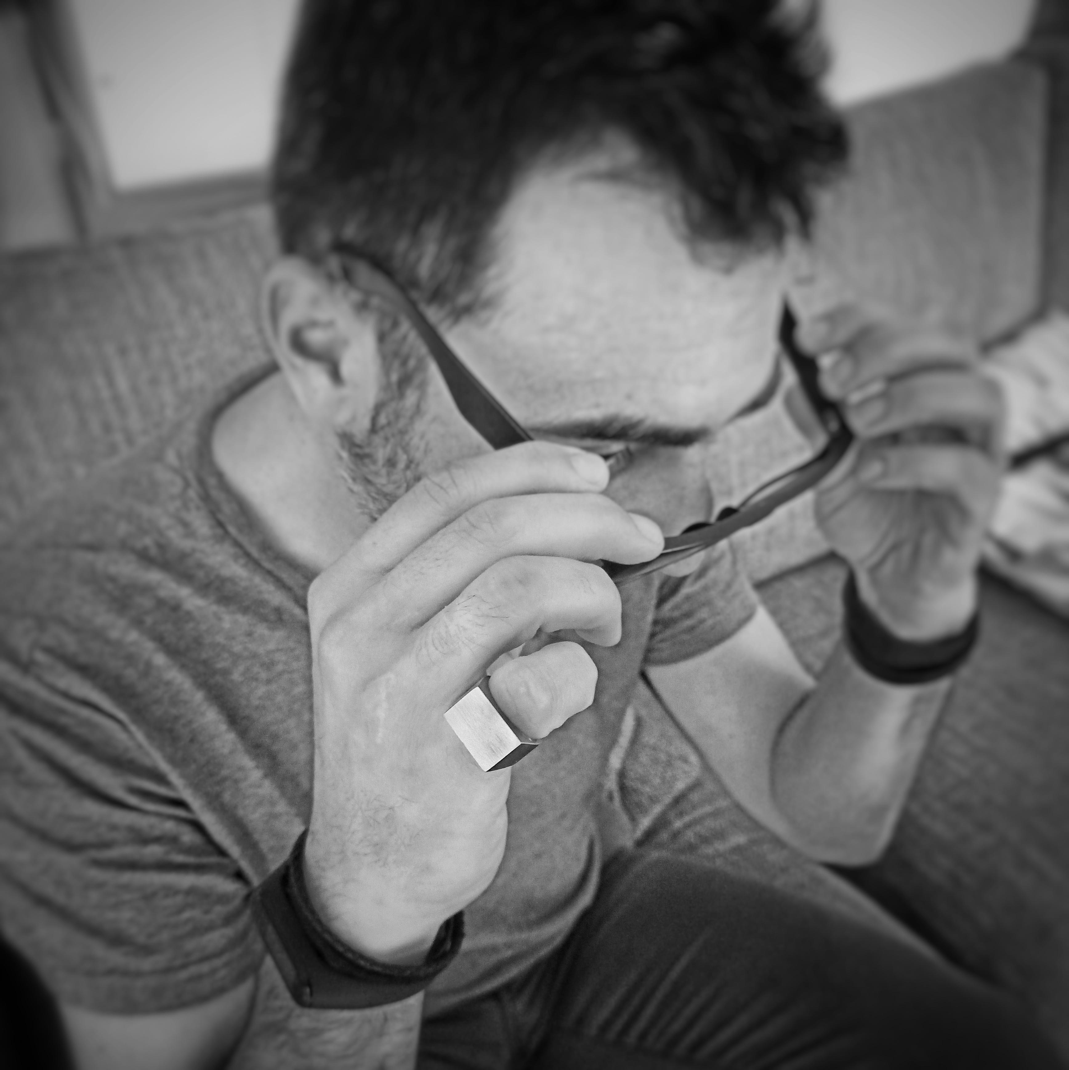 Un uomo si toglie gli occhiali e indossa sulla mano destra un anello Bullone in acciaio