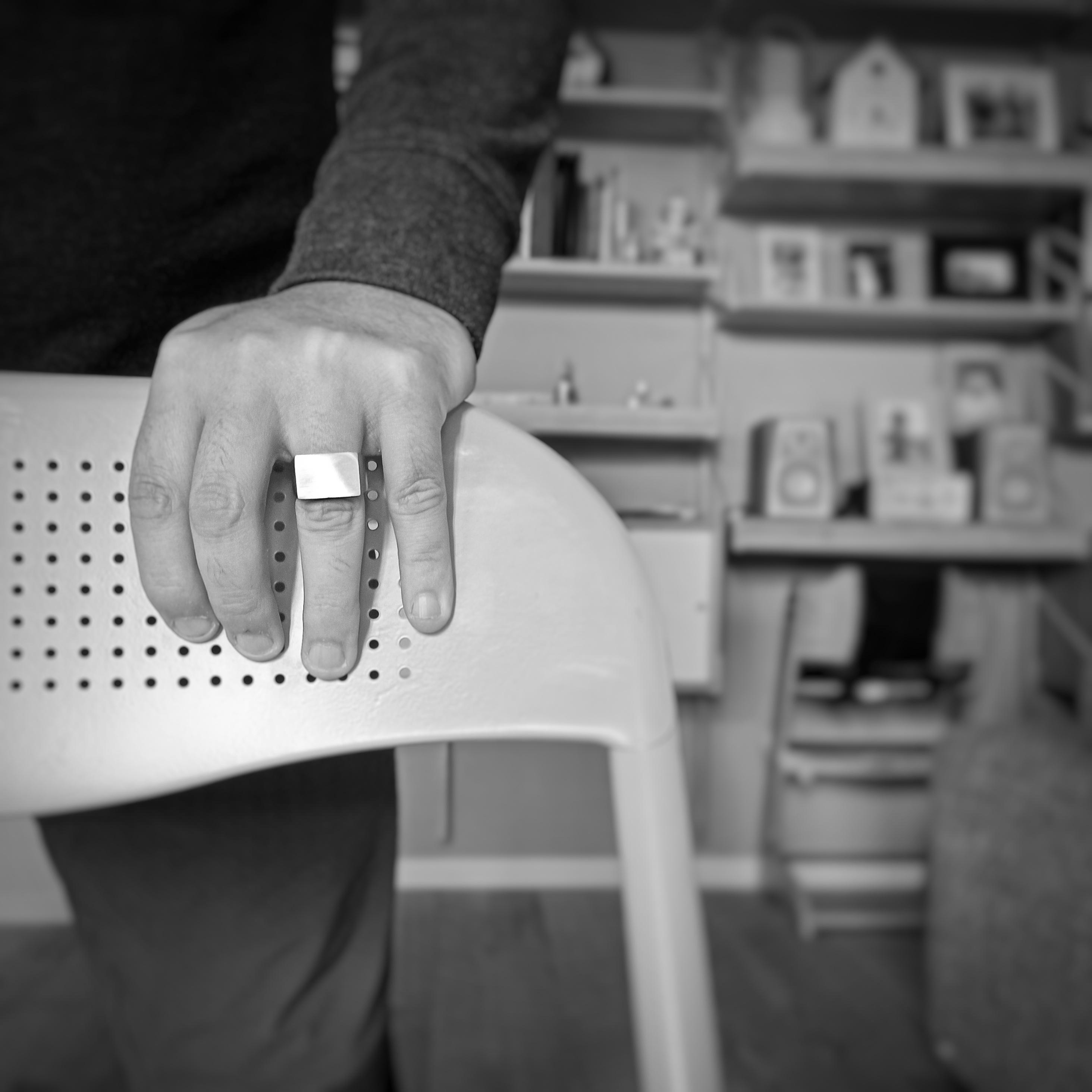 Un mano con anello Bullone appoggiata ad uno schienale di una sedia