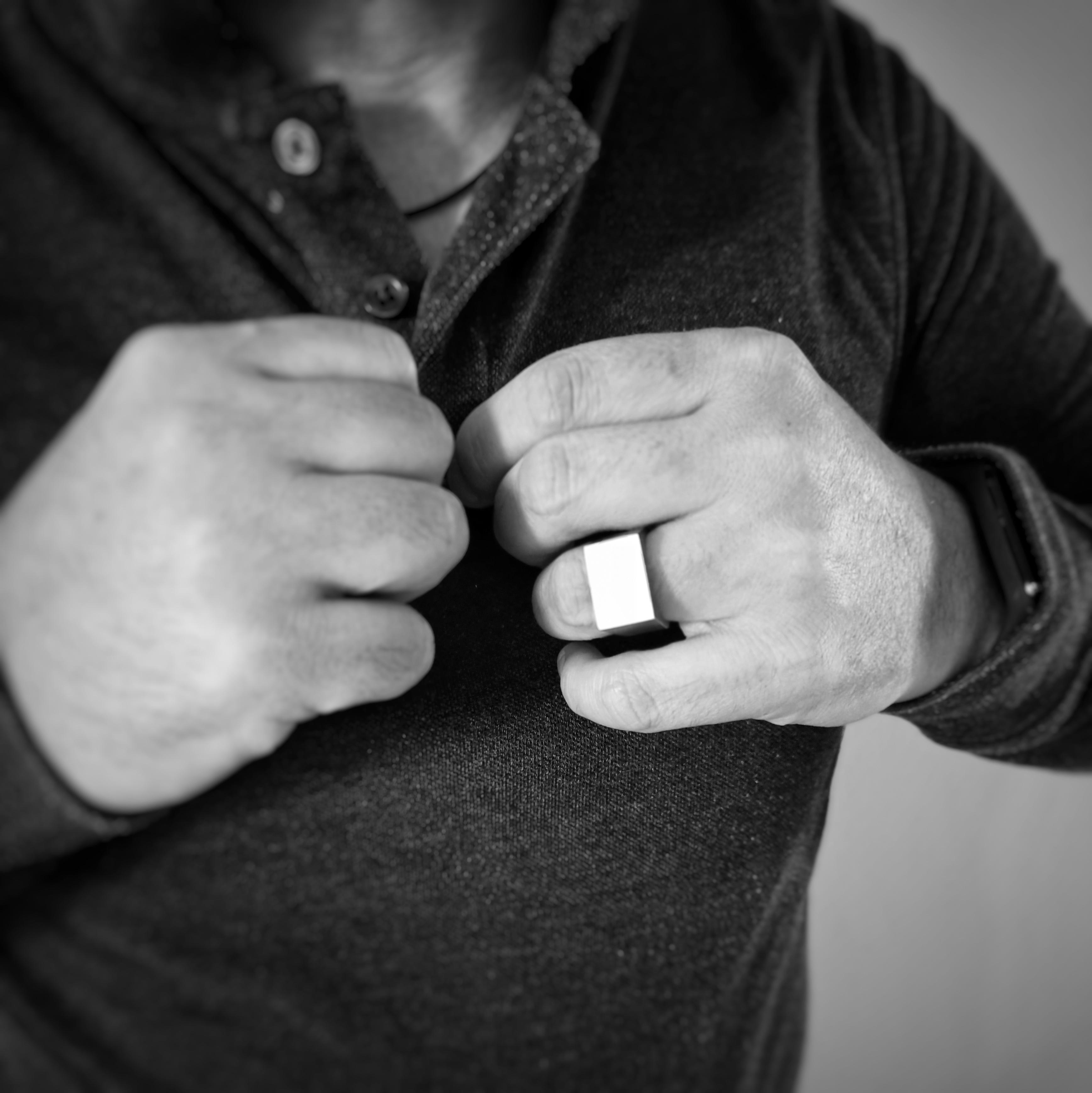 Un uomo si allaccia il colletto della polo mostrando l'anello Bullone