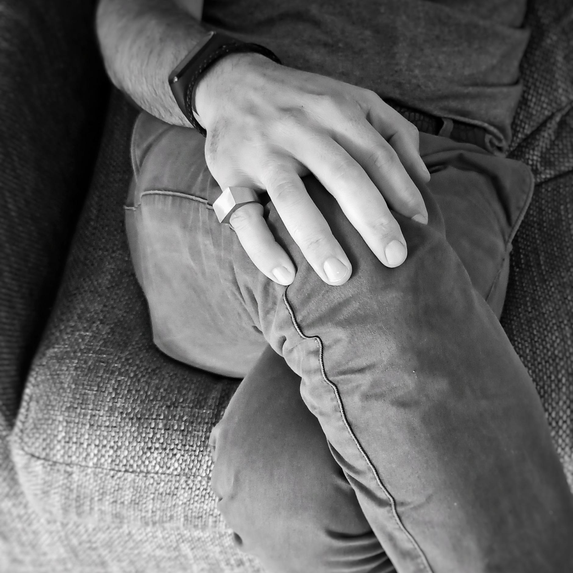 Una mano appoggiata sul ginocchio con anello Bullone in acciaio