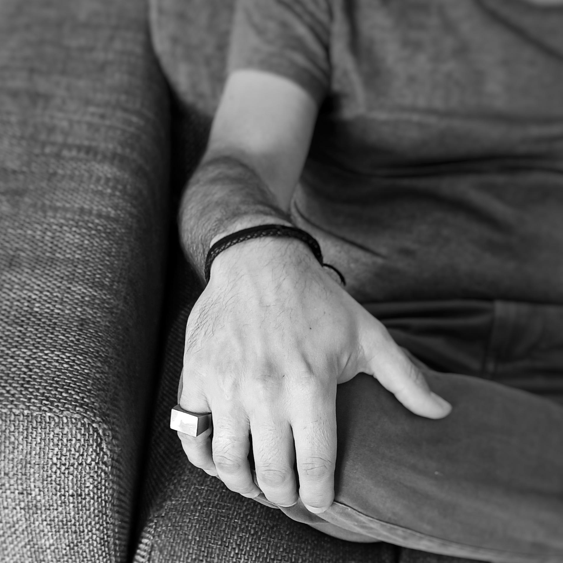 Un uomo rilassato indossa un anello in acciaio sulla mano destra