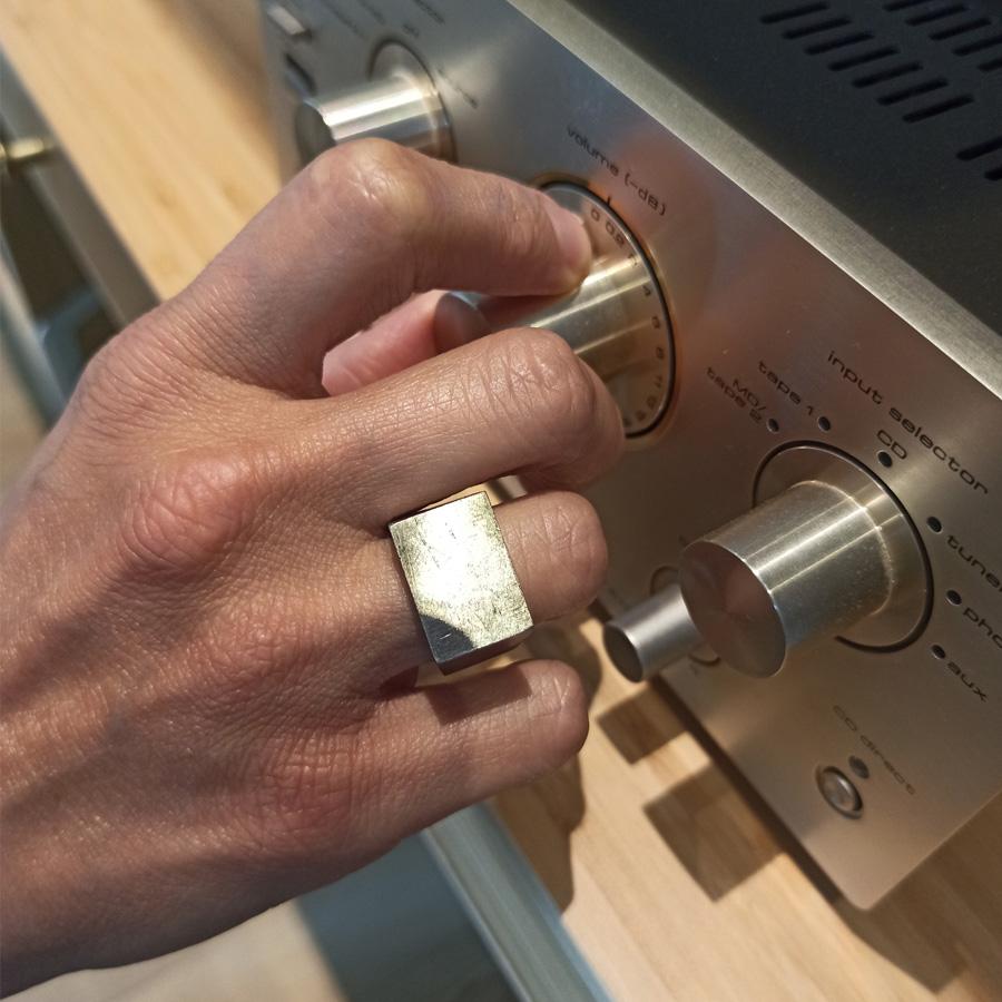 Anello unisex in acciaio indossato su una mano di donna